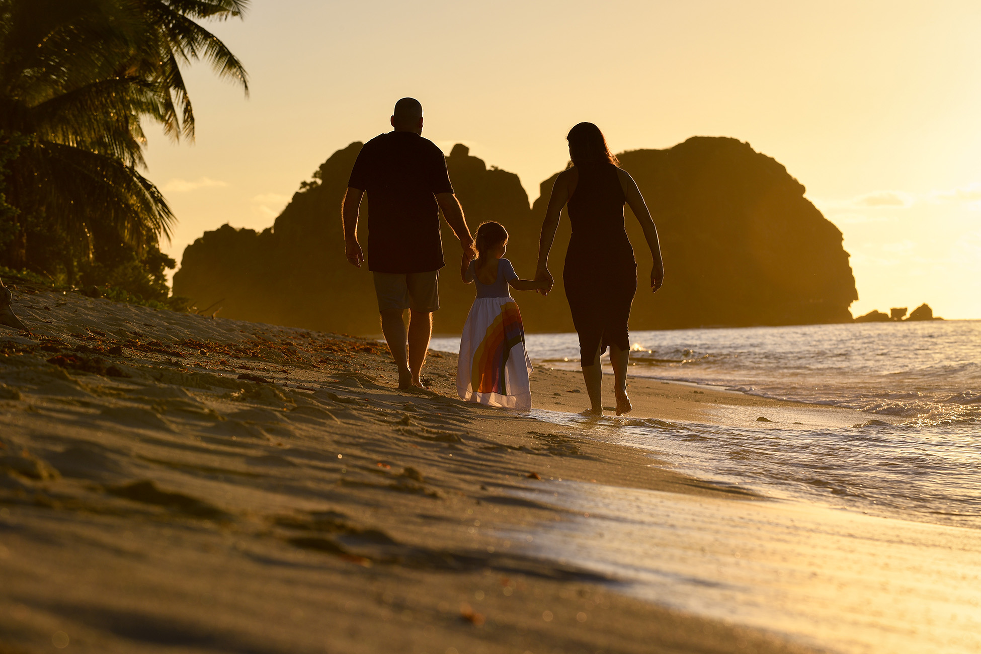 A golden haze glows on the family as they stroll on the beach at sunset