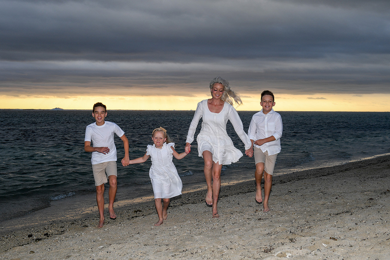 family photoshoot at the Outrigger Fiji. Mother and children running at the beach