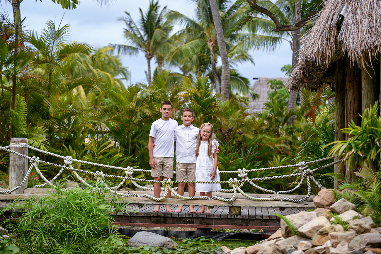 Siblings portrait posing on the bridge by the palm trees