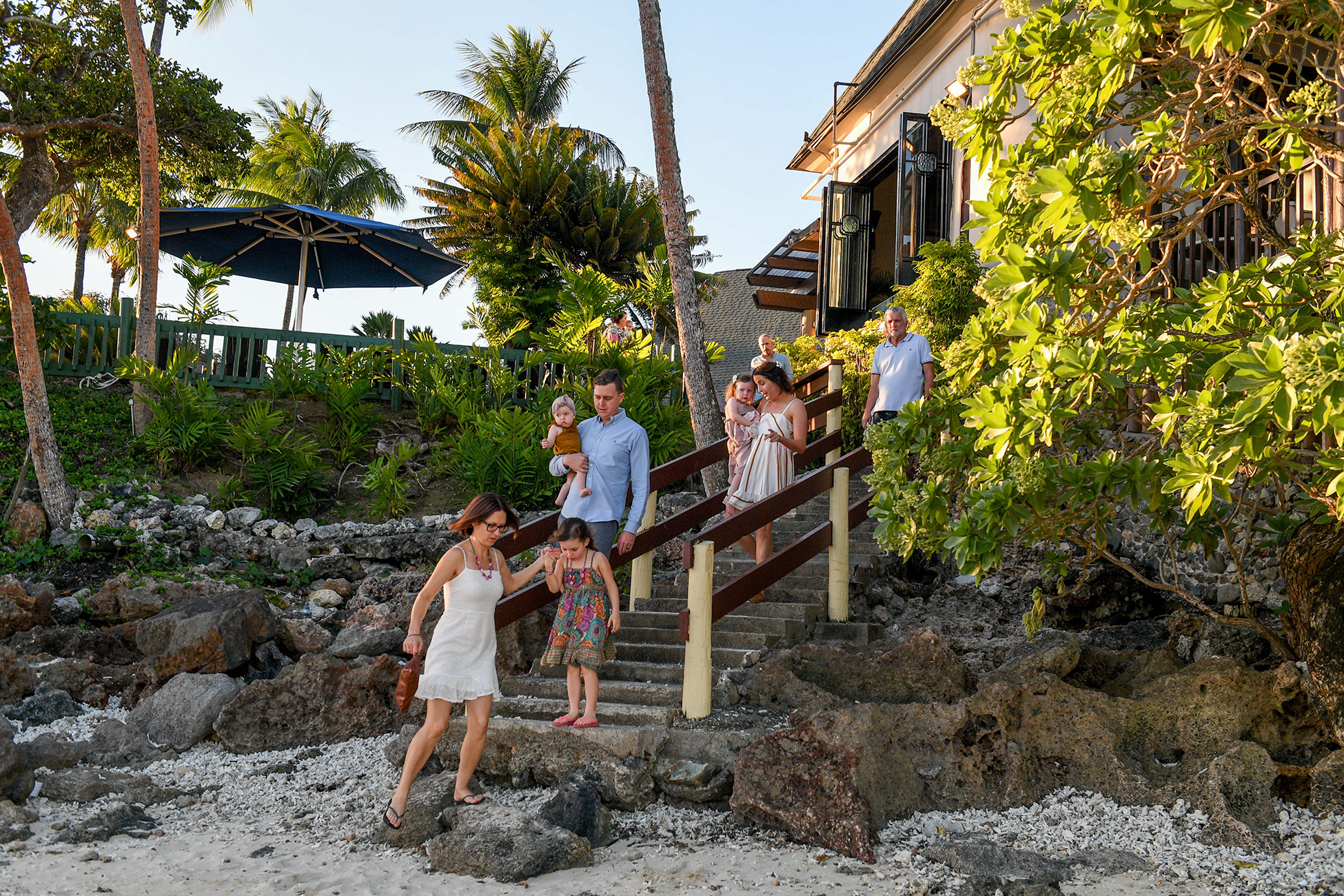 Family walking down the stairs to go to the beach in Fiji
