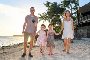 Family walking holding hands on the beach in Fiji