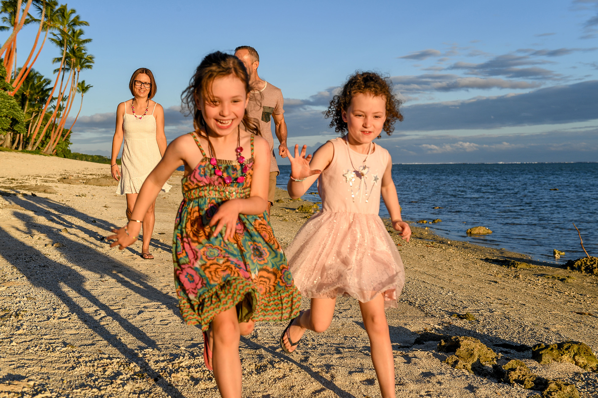 Family running and racing on the beach for a fun photshoot