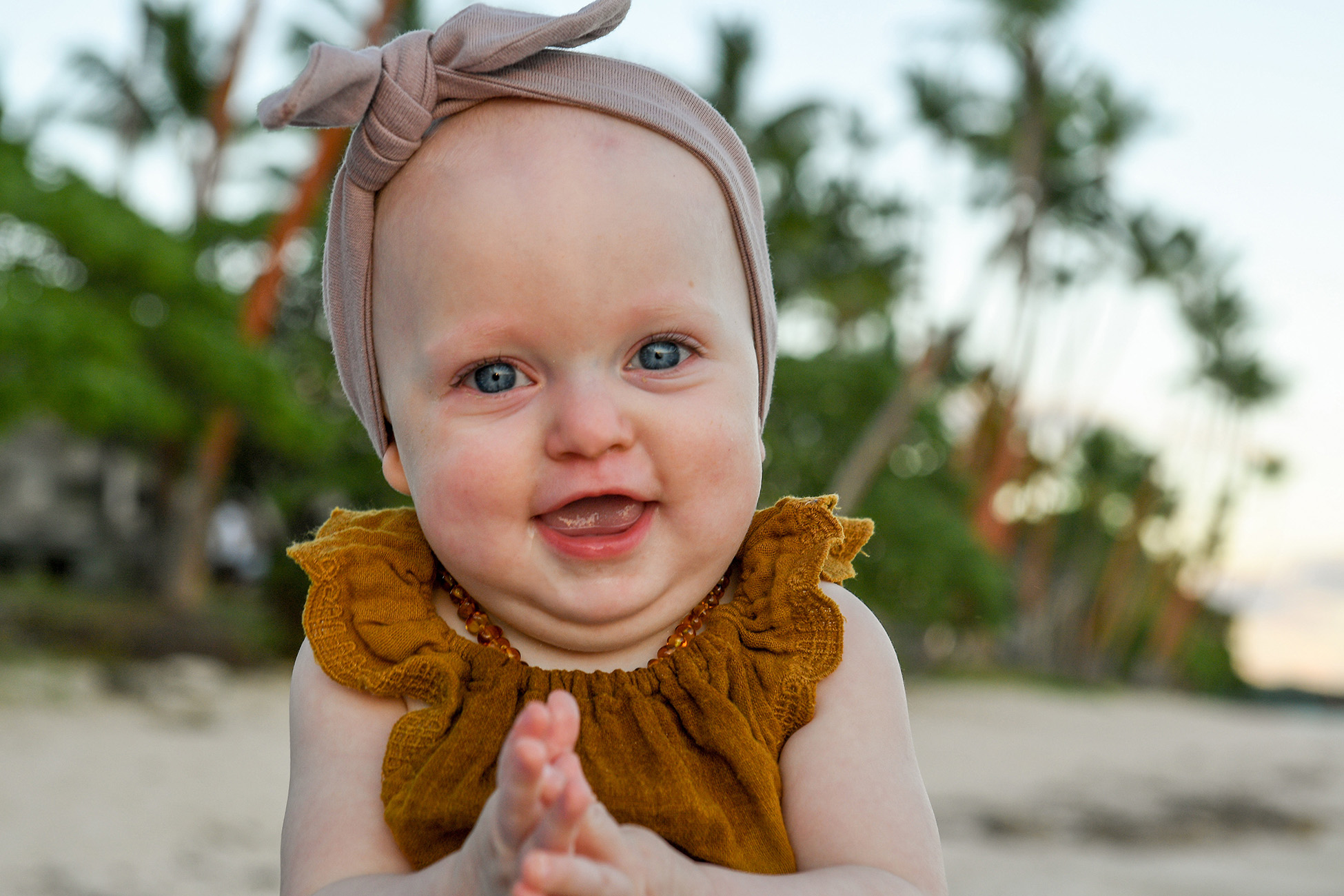 Portrait of a baby with beach and palm trees in the background